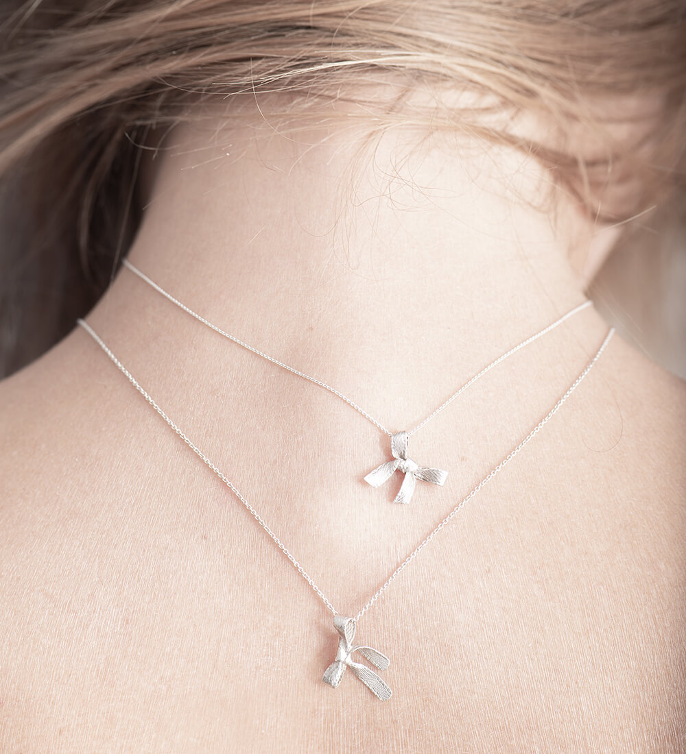 Two silver necklaces, bows